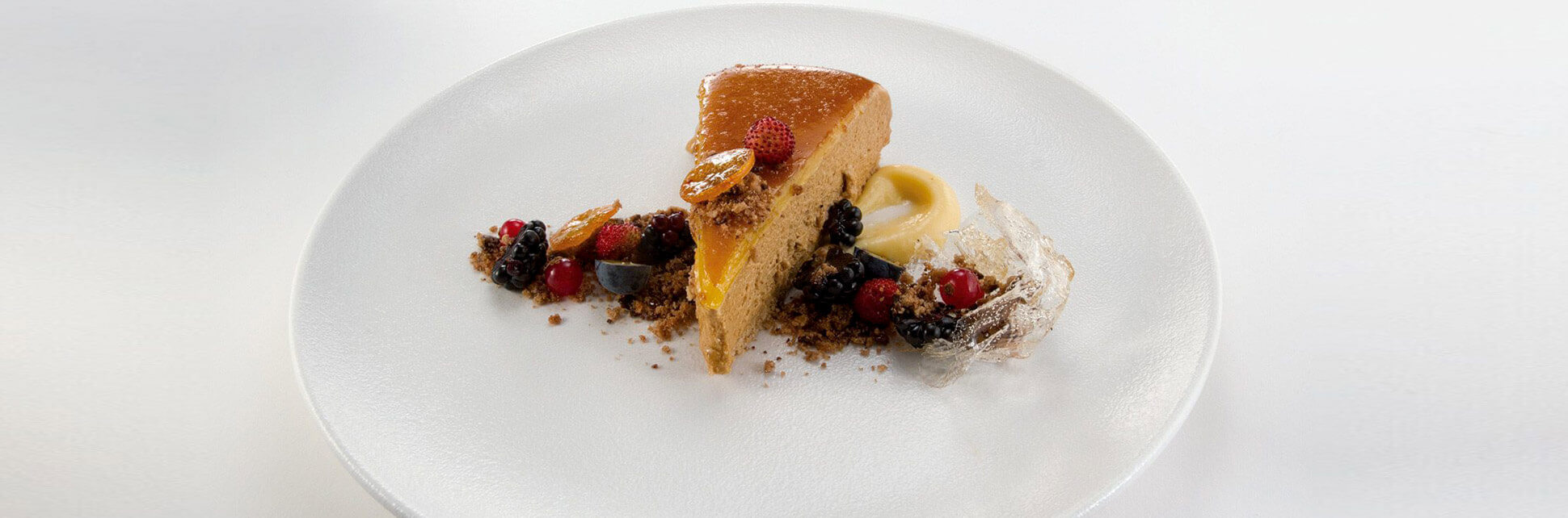 Caramel cake with spilled glass of crumble and fruit